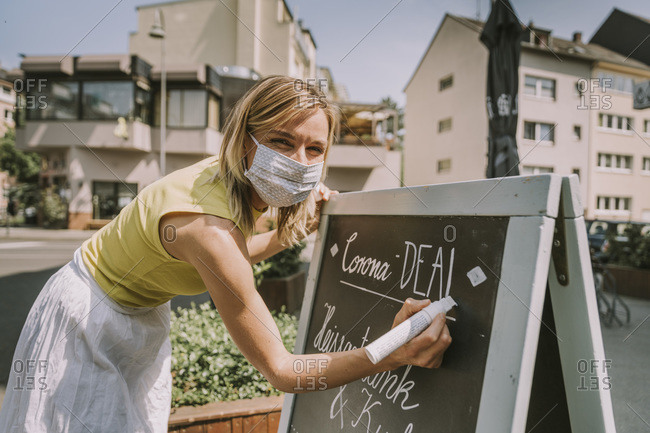 Cafe owner wearing face mask writing on board with Corona special offers