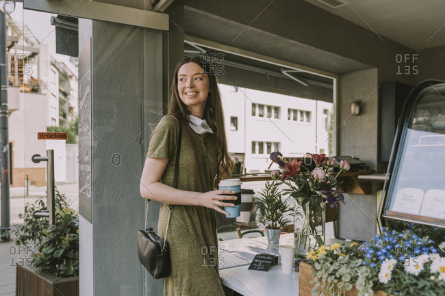 Smiling woman with let-down face mask holding two take-away coffees