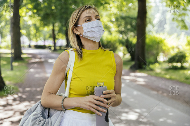 Woman in nature holding drinking bottle and wearing face mask
