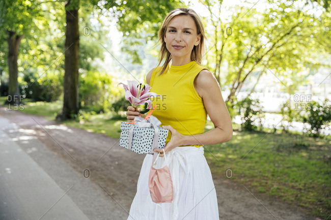 Portrait of woman in nature holding lily flower and gift