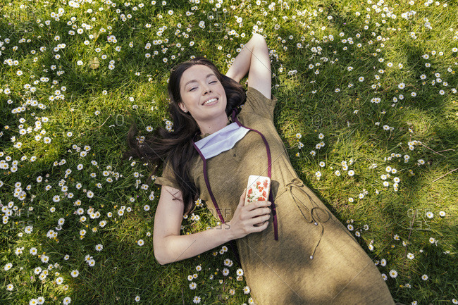 Woman with let down face mask enjoying her free time while lying on grass with daisies