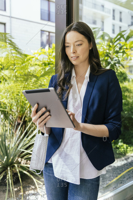 Businesswoman with face mask in hand using tablet at glass pane