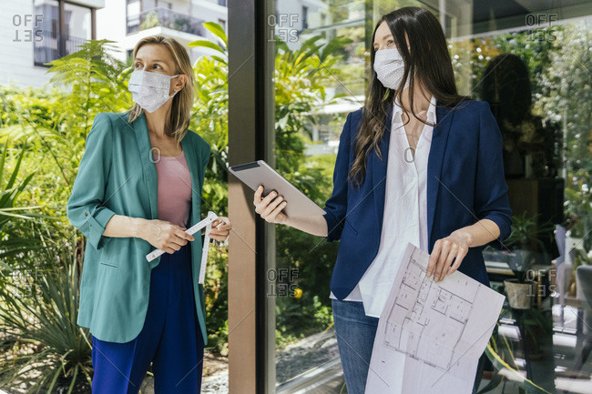 Two real estate agents wearing face masks while inspection outdoor area of house