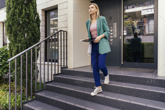 Real estate agent with digital tablet and face mask in hand walking down stairs of house