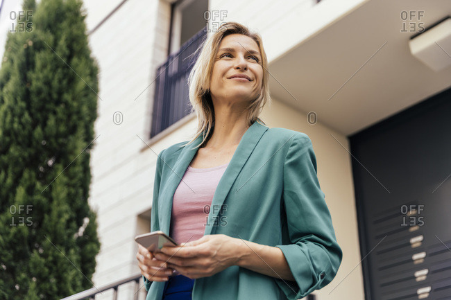 Woman with smart phone in hand at stairs of house looking around