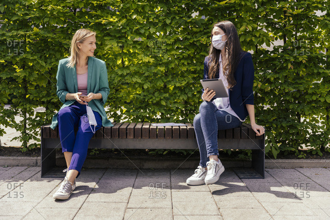 Two businesswomen sitting on bench outside and keeping their distance while wearing face mask