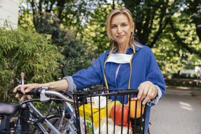 Portrait of confident woman with let down face mask and bicycle and groceries