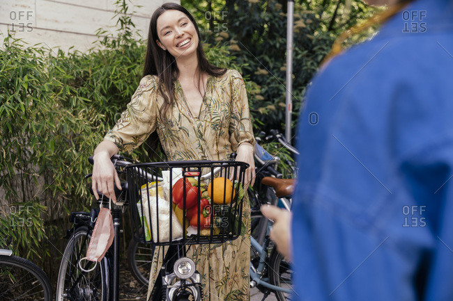 Two women with bicycle and face mask meeting in urban area