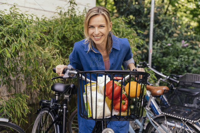 Portrait of happy woman with bicycle and groceries