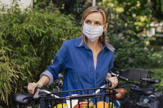 Woman wearing face mask with bicycle and shopped groceries in urban area