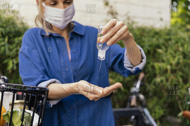 Woman with bicycle wearing face mask disinfecting her hands