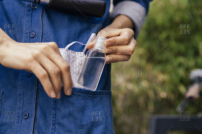 Close-up of woman putting sanitizer and face mask in pocket