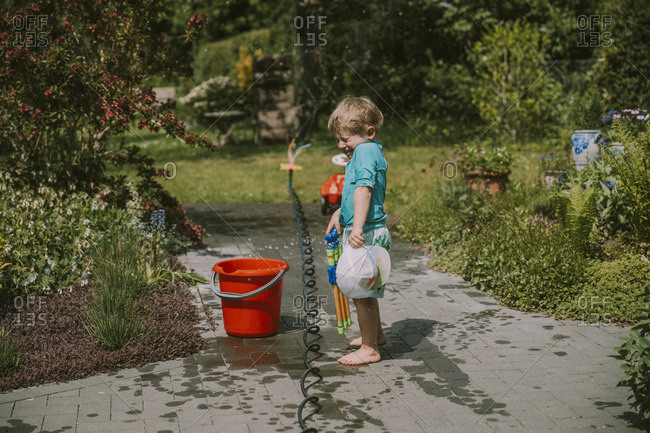 Cute boy standing by pipe and bucket on footpath in garden during sunny day
