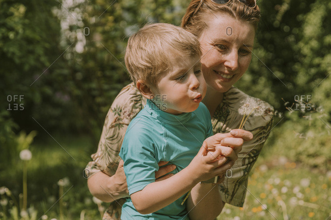 Happy woman holding son blowing dandelion seeds at garden on sunny day