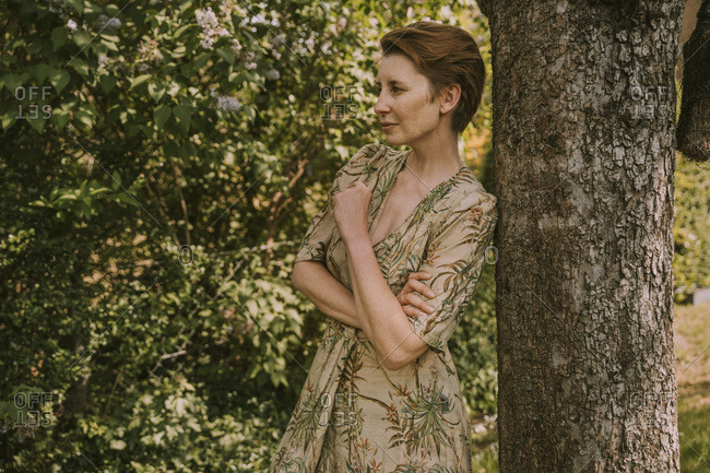 Thoughtful woman looking away while standing against tree trunk at garden