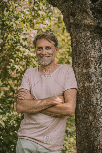 Smiling bearded mature man standing with arms crossed leaning on tree trunk at garden