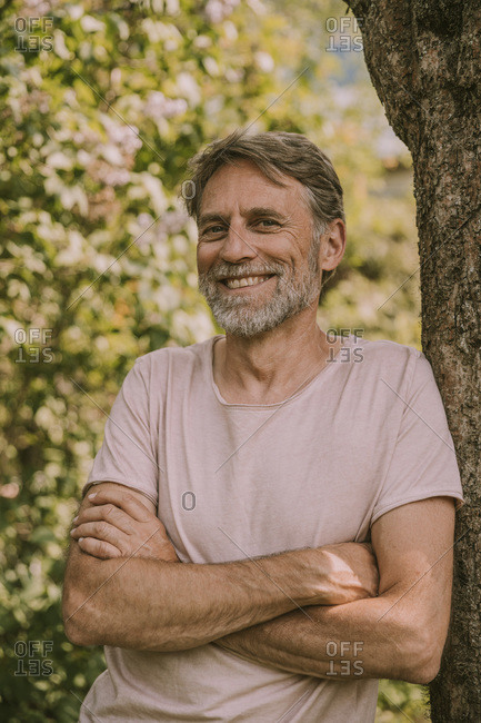 Happy bearded mature man standing with arms crossed leaning on tree trunk at garden