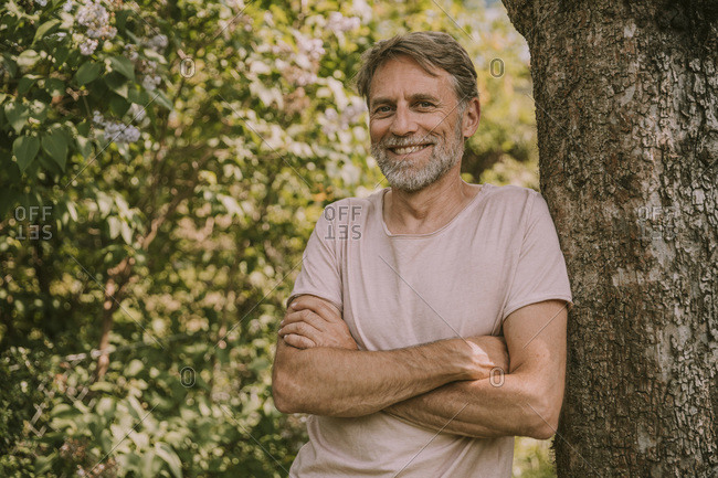 Smiling bearded man with arms crossed leaning on tree trunk at garden
