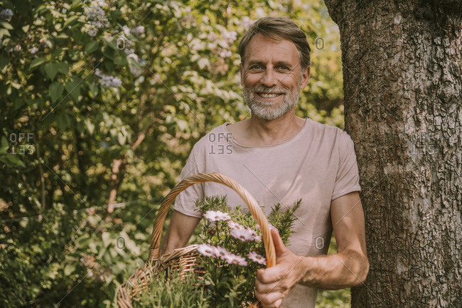 Happy bearded man holding basket with flowers and herbs while leaning on tree trunk at garden