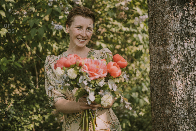 Happy woman looking away while holding fresh peony bouquet against plants at garden