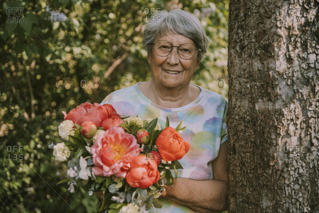Senior woman holding fresh peony bouquet by tree trunk at garden