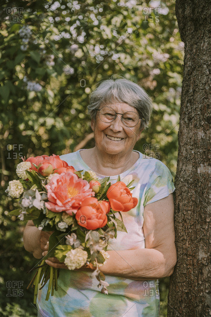 Smiling elderly woman holding fresh peony bouquet by tree trunk at garden