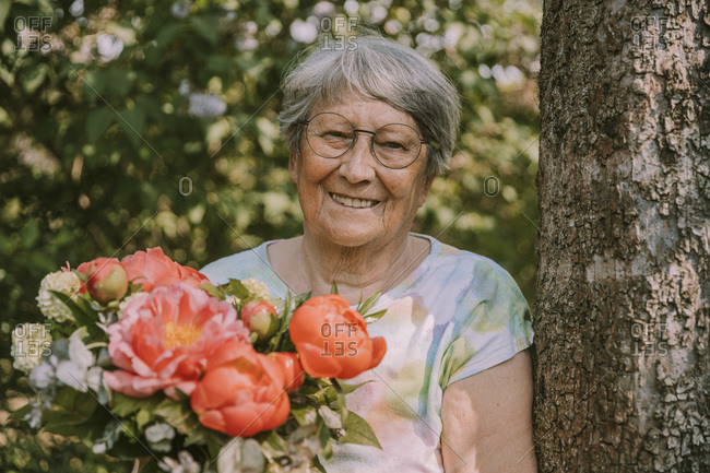 Retired senior woman holding fresh peony bouquet by tree at garden