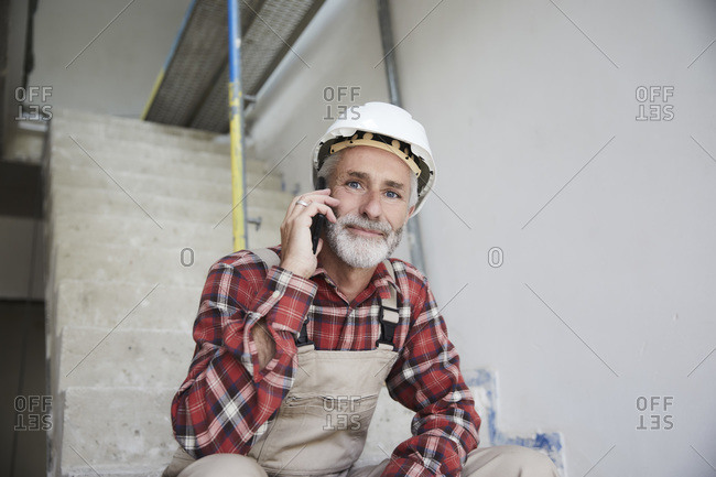 Construction worker phoning at construction site