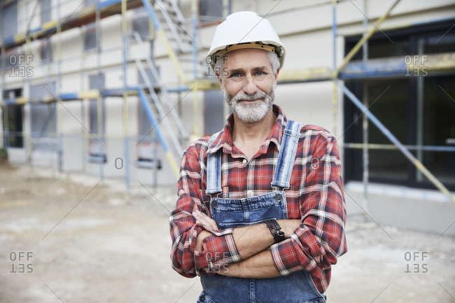 Smiling construction worker with crossed arms at construction site