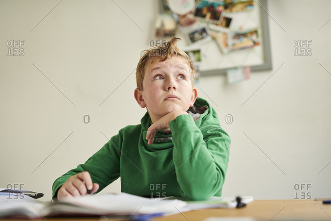 Pensive boy looking away while studying at home