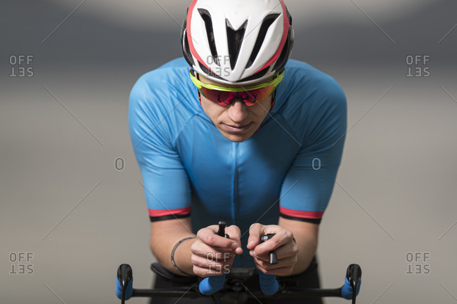 Young male athlete in sports clothing riding racing bicycle