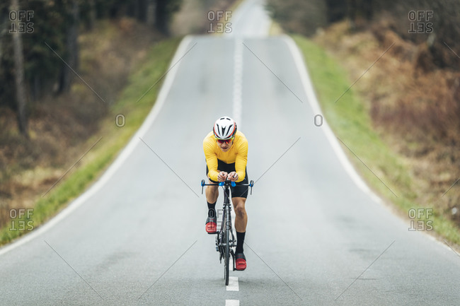Young sportsperson cycling on road