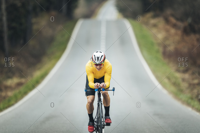 Smiling young sportsperson riding racing bicycle on country road