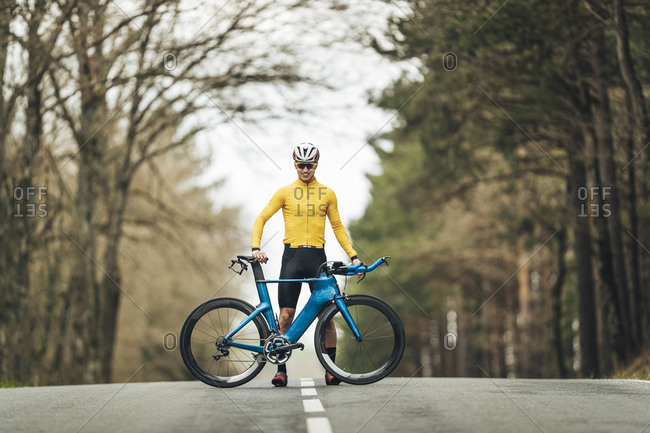 Smiling young man in sports clothing standing with mountain bicycle on country road