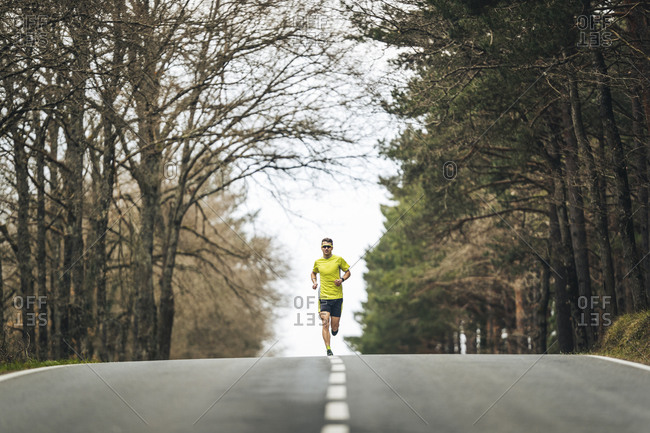 Young sportsperson running on country road amidst trees