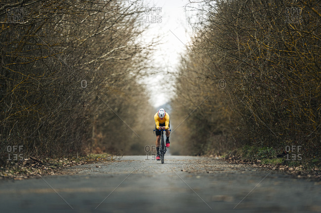 Young sportsperson riding bicycle on road amidst bare trees