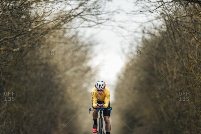 Young man riding racing bicycle amidst bare trees