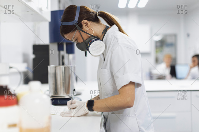 Mature female pharmaceutical technician writing data at desk in laboratory