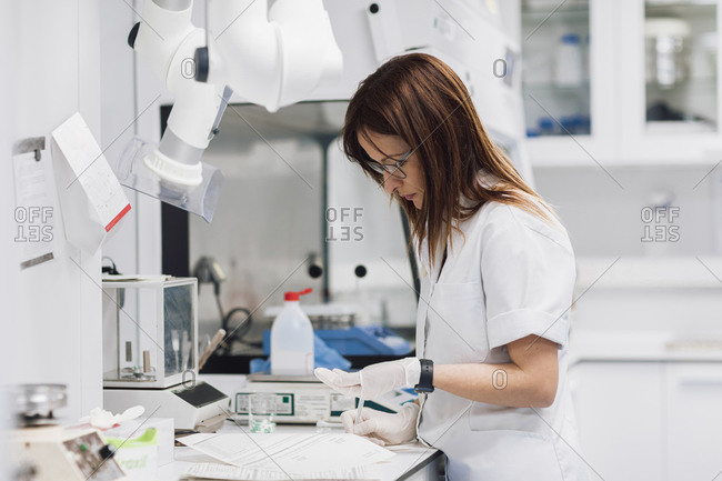 Mature female pharmaceutical technician holding pills while standing by desk at laboratory