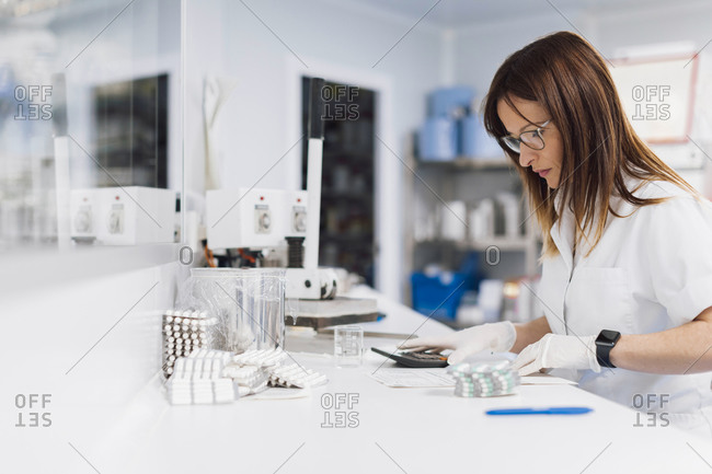 Confident mature female healthcare worker with pills and calculator at desk in laboratory