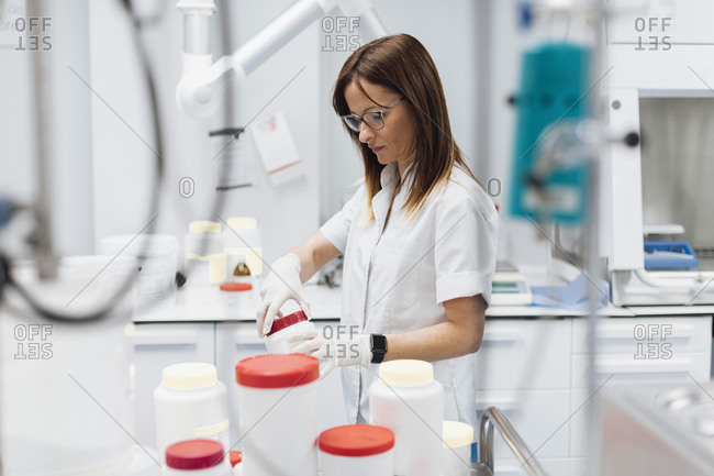 Confident female doctor opening jar while standing at laboratory