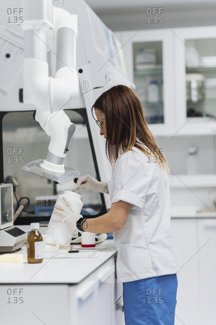 Female healthcare worker with long brown hair removing something from jar while working at laboratory