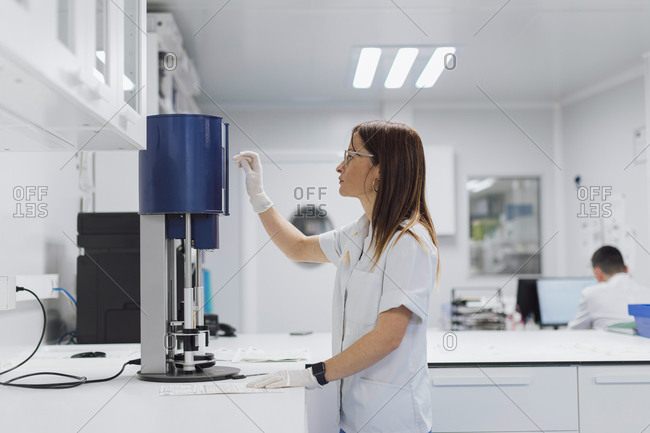 Female scientist using equipment while working at laboratory
