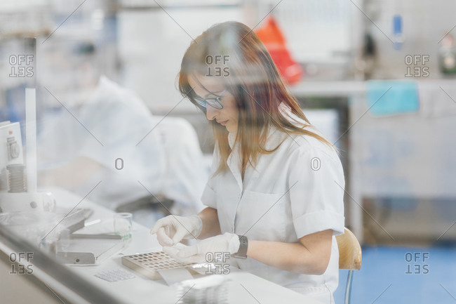 Confident female technician preparing for research seen from glass window
