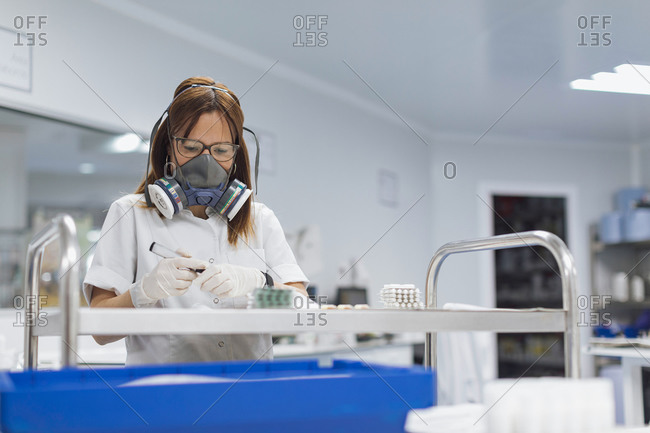 Confident mature female technician holding marker while looking at pills in lab