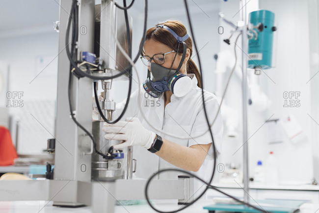 Confident female scientist using medical equipment for research at lab