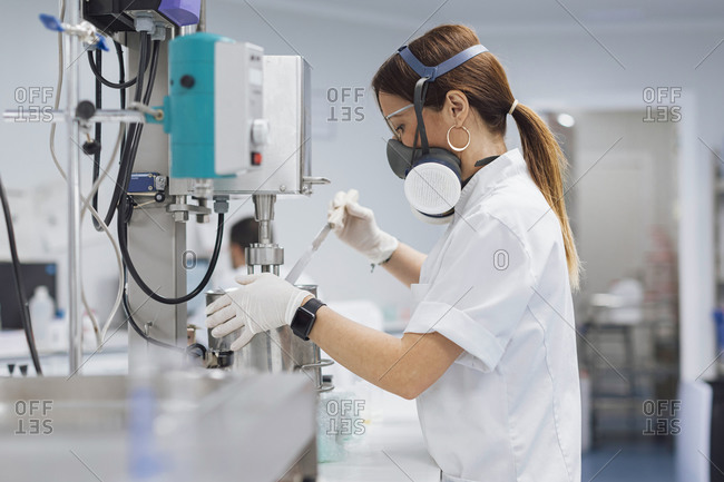 Confident female technician using medical equipment for research at lab