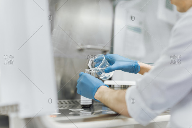 Young male technician pouring chemical from beaker while doing research at lab