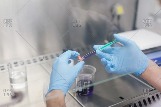 Hands of male technician holding syringe with chemical over beaker in lab