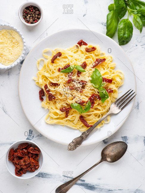 Overhead view of fettuccine pasta served with sun dried tomatoes, basil and ground cheese parmesane